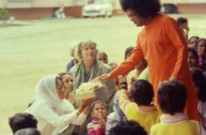 Sai Baba giving darshan - here he  is blessing gifts.