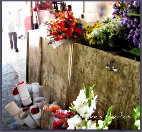 Bunches of fresh flowers lay on the floor waiting for people to buy them, most would be gone by afternoon.