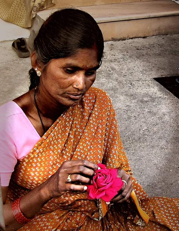 threading flowers for garlands, she is lost in contemplation