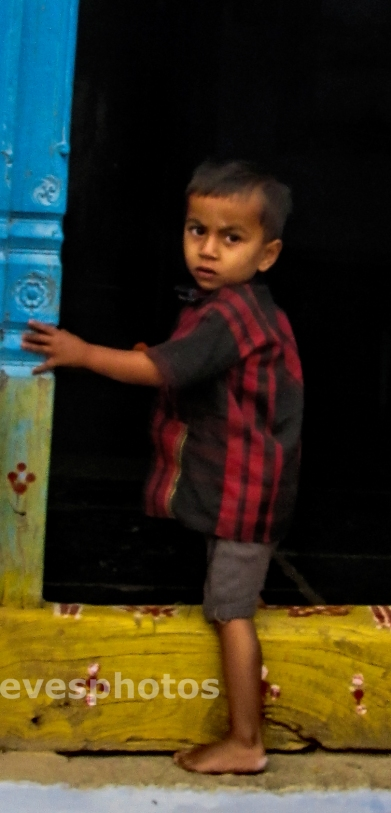little boy in Andra Pradesh village. He is stepping into his home, away from me and the camera -