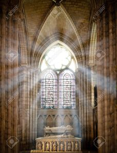 - sun rays beaming through the old stained glass window of saint denis cathedral and lighting interior with tomb. Paris, France, Europe.